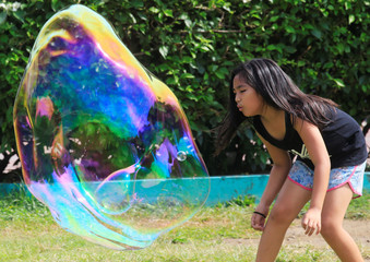 A child blows at a large soap bubble created by a street performer at Rizal park in Luneta