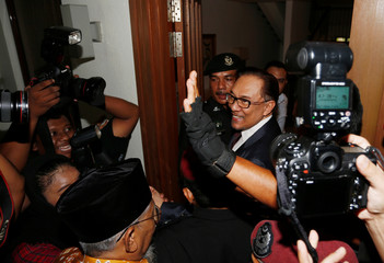 Malaysian politician Anwar Ibrahim arrives at his home after he was granted a full pardon by Malaysia's King Sultan Muhammad V, in Kuala Lumpur