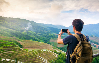 Man taking picture of stunning Asian rice terrace landscape