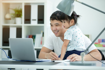 Asian family and little girl ,while dad works with notebook on work table.