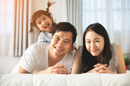 Happy asian family father mother with daughter looking camera with smile face.