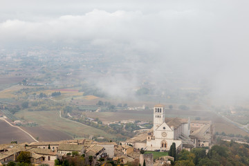 View of St. Francis papal church in Assisi (Umbria, Italy) in the middle of lifting morning fog
