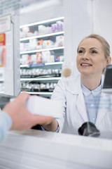 Serious medication. Low angle of glad female pharmacist giving medication and smiling
