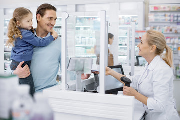 Photo sur Plexiglas Pharmacie Your medication. Successful female pharmacist passing medication and man holding girl