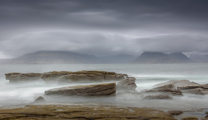Long exposure seascape panorama at the western coast of the Isle of Skye - dark and mysterious image with rocks in the foreground and storm clouds hanging over the mountains in the background