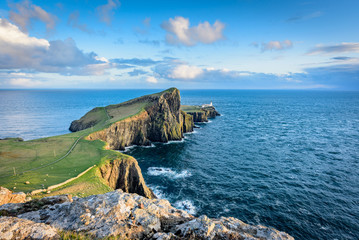 Neist Point lighthouse at sunset on a bright sunny day with clear waters, dramatic sky, gentle rays of sunlight over green grass and jagged rocks - typical Scottish landscape
