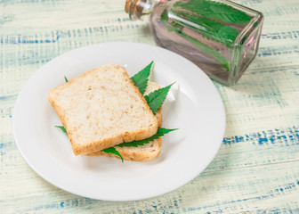 Marijuana and food. A sandwich with marijuana leaves. The use of cannabis in the manufacture of food. The concept of increasing appetite after consuming marijuana.