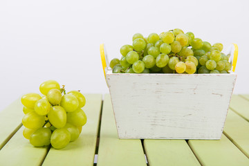 basket with grapes. White basket with green grapes
