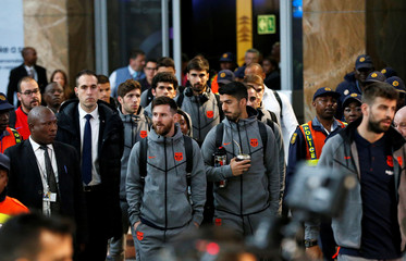 Barcelona's Argentine soccer star Lionel Messi arrives with teammates for the Nelson Mandela Centenary Challenge against South Africa's Mamelodi Sundowns at the FNB Stadium, in Johannesburg