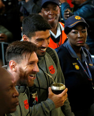 Barcelona's Luis Suarez and Lionel Messi share a joke as they arrive with teammates for the Nelson Mandela Centenary Challenge against South Africa's Mamelodi Sundowns at the FNB Stadium, in Johannesburg