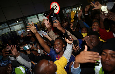 Suppoters cheer as they welcome Barcelona's soccer team during their arrival for the Nelson Mandela Centenary Challenge against South Africa's Mamelodi Sundowns at the FNB Stadium, in Johannesburg