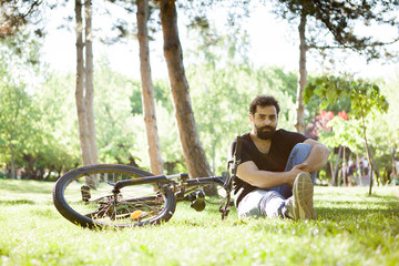Young bearded man sitting on the grass in the park next to his bicycle