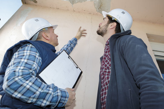 builder inspecting roof damage