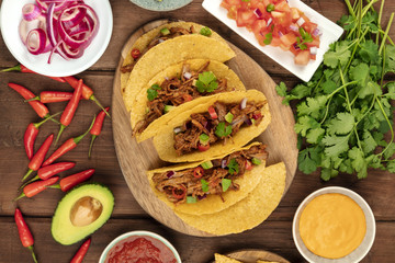 Overhead photo of Mexican tacos with pulled meat, avocado, chili peppers, cilantro, cheese sauce