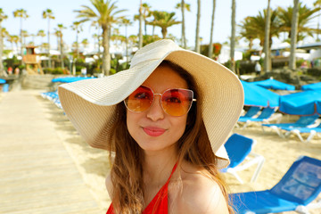 Close-up of attractive girl with long hair standing on the beach. Girl smiling to camera and shows her cool look. Straw hat on head. Palms trees on the background. Lanzarote, Canary Islands, Spain.