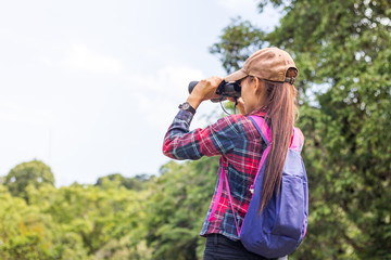 A female tourist sits on a rock using a binoculars to see the beautiful nature.