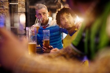 Soccer fans are sitting at the counter in the pub and are having a deep and friendly conversation about whose team is better, while drinking draft beer.