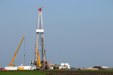 land oil drilling rig and cranes heavy machinery in the field