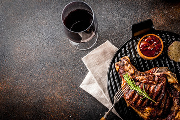 Fresh grilled meat beef steak with with red wine, herbs and spices. Top view copy space dark rusty background