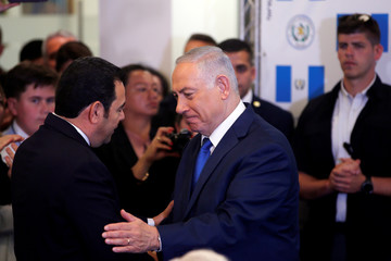 Israeli Prime Minister Benjamin Netanyahu shakes hands with Guatemalan President Jimmy Morales during the dedication ceremony of the embassy of Guatemala in Jerusalem
