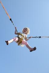 blondes mädchen beim bungee trampolin springen