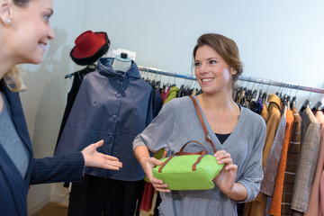 happy woman selecting handbag in commercial centre