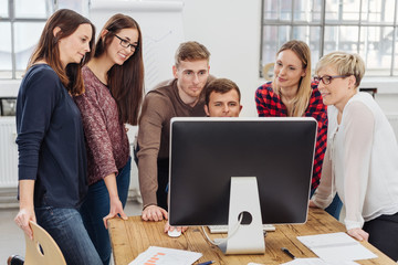 Young business team working together on a computer