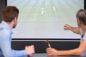 men watching a match on a big flat screen tv