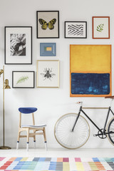 Blue and white chair and bicycle standing in white room interior with colorful carpet, gold lamp and gallery with simple posters