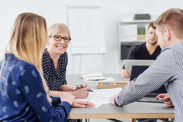 Smiling woman in a meeting with co-workers