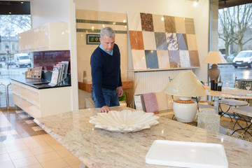 man touching different finishes in modern kitchen shop