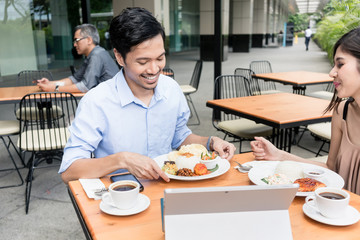 Young Asian man and woman smiling while having lunch together outdoors at a modern cafeteria downtown in summer