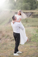 beautiful love people, newlyweds, a young couple, outdoor session. The bride in a white dress. Love, wedding, passion. whirling, carrying on hands