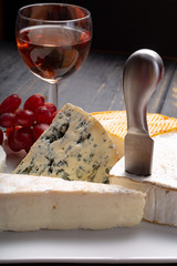 French cheeses plate in assortment, blue cheese, brie, munster, soft goat cheese, Neufchatel served with rose wine