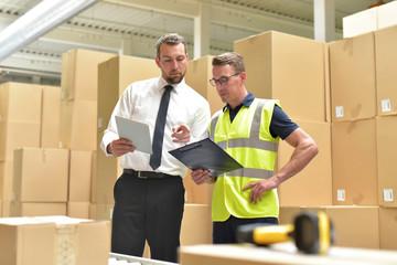 Arbeiter und Geschäftsmann bei einer Besprechung im Warenlager eines Versandhandels // Worker and businessman at a meeting in the warehouse of a mail-order company