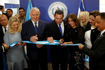 Hilda Patricia Marroquin, the wife of Guatemalan President Jimmy Morales, cuts the ribbon during the dedication ceremony of the embassy of Guatemala in Jerusalem, as she stands with Guatemalan President Jimmy Morales, Israeli Prime Minister Benjamin Netany