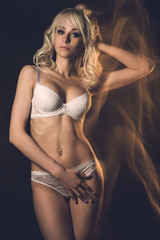 Slim sexy young blond woman posing in white lace lingerie