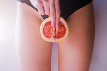A woman is holding a grapefruit by her panties. Concept masturbation