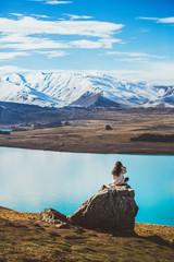 A girl with long hair sit on a rock looking at Lake Tekapo