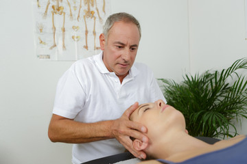 Osteopath holding woman's head