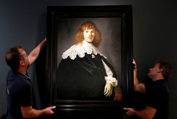 "Gallery assistants hold a Rembrandt painting called ""Portrait of a Young Man"" at Hermitage Amsterdam"