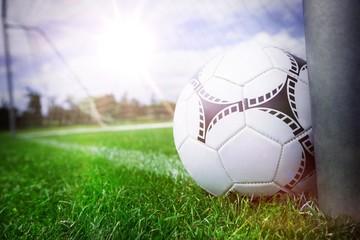 Close-up of soccer ball near a goal post