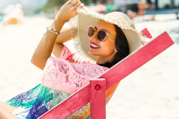 Beautiful girl sitting on the beach by the sea in the color deck chair, dressed in a pair of straw hat with sunglasses, summer vacation trip, emotion joy happiness
