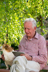 Old man with dog and tablet crying in garden