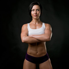 Girl. Fitness model in white top, on a black background.