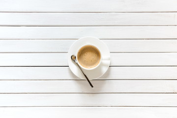 White cup of coffee on a white wooden rustic background. Flat lay, top view, copy space