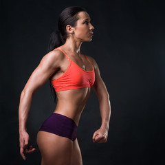Girl. Fitness model in an orange top, on a black background.