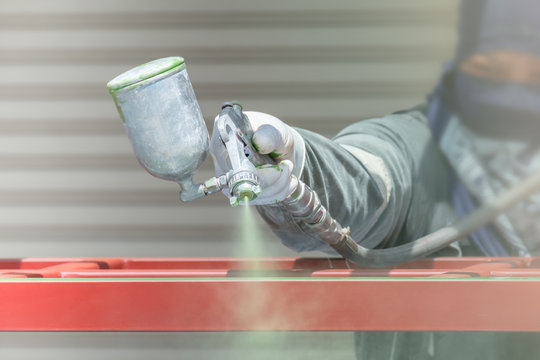 Workers spraying paint on metal work.