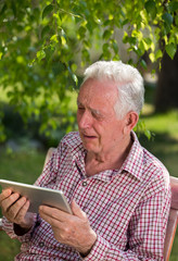 Old man with tablet crying in garden