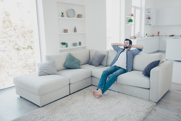 Full-size portrait of meditative  trendy single man with stubble in jeans shirt sitting on sofa in modern livingroom holding hands behind the head with close eyes enjoying free time